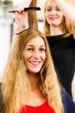 På frisören - kvinnan får ny hårfärg Arkivbilder