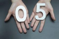 På gömma i handflatan numret noll och fem Fotografering för Bildbyråer