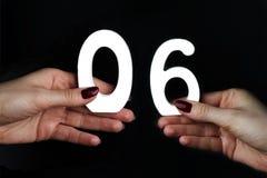 På gömma i handflatan numret noll och sex Arkivfoto