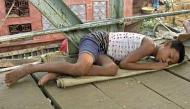 På gatan som sover den hemlösa pojken, gatabarn royaltyfri fotografi