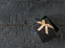 På glänt svart gåvaask med pilbågen på trätabellen royaltyfri fotografi