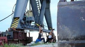 På gryning nära lastkranen två unga härliga idrotts- flickor som gör övning med trxupphängningremmar Kondition lager videofilmer