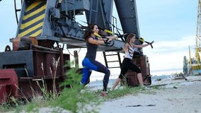 På gryning nära lastkranen två unga härliga idrotts- flickor som gör övning med trxupphängningremmar Kondition arkivfilmer