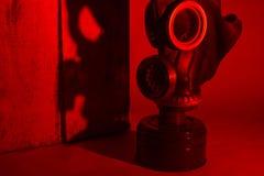 På hög nivå av fara Skuggan från gasmasken med membranet faller på hörnet av träasken i rött ljus Hårt förfärligt arkivfoto