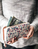 På handväskan för kvinna` som s ut klibbar $ 100 Tryck av blommor Händer för kvinna` s med en trevlig manikyr Affärserbjudanden Royaltyfri Foto