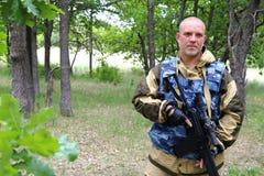 På jakten En jägare för militär man står med ett skjutvapen in royaltyfri foto