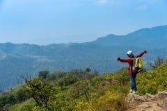 På kanten av en stenig klippa lyfter kvinnor hans händer till himmel som ett tecken av frihet eller segern och i bakgrunden ett f royaltyfri foto