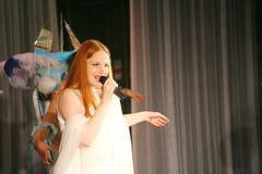 På konsertetappen i en vit klänning ledningssångaren av musikbandmintkaramellen, överdådig vokalist Anna Malysheva Rött Royaltyfria Foton
