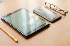 På lekmanna- exponeringsglas för tabell och en minnestavla, en smartphone och en blyertspenna Fotografering för Bildbyråer