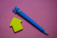 På monophonic ljus rosa bakgrund den ovanliga blåa pennan med huvudet av hjortar Närliggande lögnklistermärkear, anmärkning royaltyfri fotografi