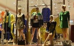 På natten shoppar 5 vintermodeskyltdockor i klänning fönstret Arkivfoton