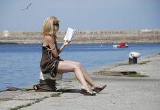 På pirflickan som läser en bok och solbada royaltyfri foto