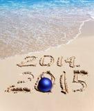 På sand är det skriftlig 2014, och 2015 och bollen för nytt år ligger Arkivbild