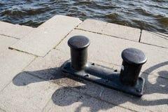 På skeppsdockan på porten gammalt gjutjärn som förtöjer pollare på graniten royaltyfri bild