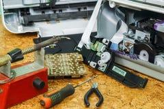 På skrivbordet är demonteraa utrustning och hjälpmedel för reparation royaltyfri fotografi