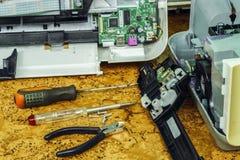 På skrivbordet är demonteraa utrustning och hjälpmedel för reparation royaltyfri bild