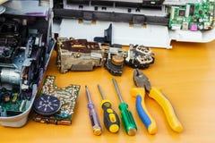 På skrivbordet är demonteraa utrustning och hjälpmedel för reparation arkivfoto