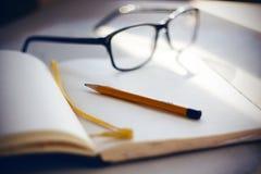 På skrivbordet är exponeringsglas, en anteckningsbok och en blyertspenna royaltyfri foto