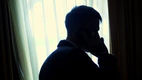 På skymning i mörkret mitt emot fönstret den stiliga mannen, affärsmannen i en vit skjorta och det blåa omslaget rymmer lager videofilmer