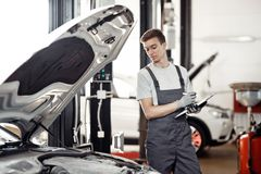 På slutet av arbetsdags: ett ungt automechanic ser resultaten av hans arbete arkivbild