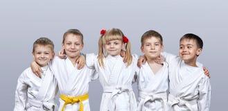 På små idrottsman nen för en grå bakgrund i karategi Arkivfoton