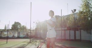 På solig dag en gullig dam på tennisbanan som dacing, innan att starta leken som rymmer i hand tennisracket arkivfilmer