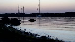 På solnedgången fortskrider yachten floden arkivfilmer