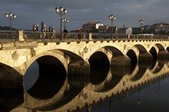 På soluppgång vallfärdar går över den välvda bron Royaltyfri Foto