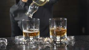 På stångräknaren Oigenkännlig kvinnlig bartender i hällande whisky för svart skjorta in i grej i ultrarapid coctail stock video