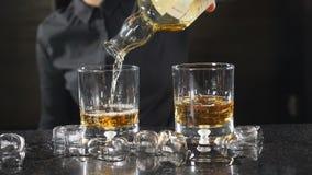 På stångräknaren Oigenkännlig kvinnlig bartender i hällande whisky för svart skjorta in i grej i ultrarapid coctail lager videofilmer