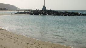 På stranden Två kvinnor som går, köra för två män stock video