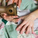 På symaskinen broderar flickan Royaltyfri Fotografi