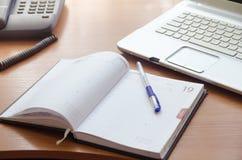 På tabellen är en bärbar dator, en detaljerad anteckningsbok med pennan och landlinetelefonen arkivfoto