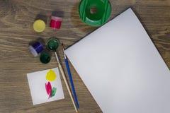 På tabellen är en uppsättning för att dra: en borste, gouache och ett vitt ark av papper På en borstegräsplanmålarfärg arkivbilder