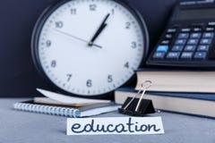 På tabellen är ett tecken med utbildning, på bakgrunden av en klocka, böcker, en räknemaskin, en notepad och ett gem Royaltyfria Bilder