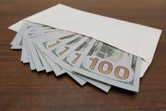 På tabellen är ett vitt kuvert som det finns många hundra dollarräkningar i Begreppskorruption, kränkning av lagen som är finansi royaltyfri foto