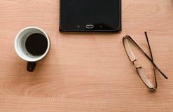 På tabellen är exponeringsglas och en minnestavla som står en kopp kaffe Royaltyfri Fotografi