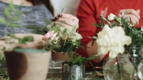 På tabellen är mycket små krukor med blommor, och i bakgrund två sitter arbetar flickorna och med blomsterhandlare, i att passera arkivfilmer