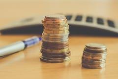 På tabellen är mynt och en räknemaskin arkivfoto