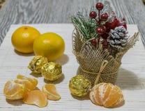 På tabellen är skivor av mandarinen, godisen och julgarnering arkivfoton