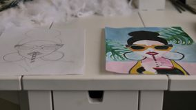 På tabellen är två ark av papper med skissar och att dra av en flicka med exponeringsglas som dricker en drink med hjälpen av ett lager videofilmer
