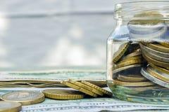På tabellen, de pappers- pengarna och en glass bank med encentmynt royaltyfria foton