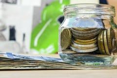 På tabellen, de pappers- pengarna och en glass bank med encentmynt royaltyfri foto