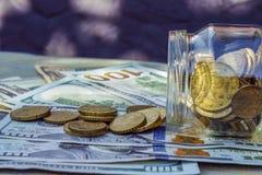 På tabellen, de pappers- pengarna och en glass bank med encentmynt royaltyfria bilder