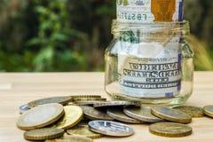 På tabellen, de pappers- pengarna och en glass bank med encentmynt royaltyfri fotografi