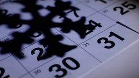 På tabellen det nya årets är den December kalendern på bakgrunden av skuggan av en snöflinga, det nya året 2019 arkivfilmer