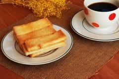 På tabellen finns det ett svart kaffe i exponeringsglaset, en frasig bulle Royaltyfri Fotografi