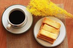 På tabellen finns det ett svart kaffe i exponeringsglaset, en frasig bulle Royaltyfria Bilder
