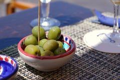 På tabellen i det medelhavs- kafét finns det en liten platta med gröna stora skinande oliv På tabellen färgar annat ljust arkivbild
