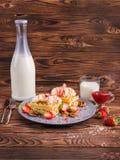 På tabellen mjölkar en flaska av efterrätten och ett exponeringsglas av och jordgubbedriftstopp royaltyfri foto